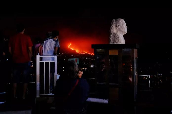 População observa enquanto lava escorre de vulcão em La Palma — Foto: AP Photo/Daniel Roca