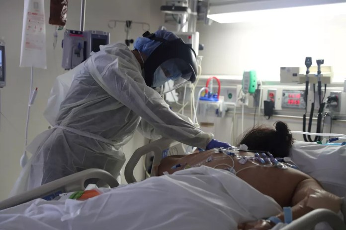 Profissional de saúde trata paciente com Covid-19 deitada de bruços em hospital em Chula Vista, na Califórnia, no dia 12 de maio. — Foto: Lucy Nicholson/Reuters