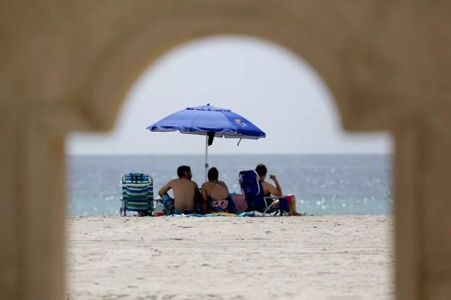 Pessoas se sentam sob o mesmo guarda-sol em Hollywood Beach, na Flórida, na quinta-feira (2)  — Foto: Lynne Sladky/AP