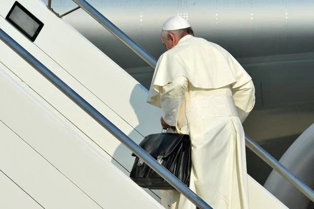 O Papa Francisco leva sua própria bagagem de mão ao embarcar para o Brasil, nesta segunda-feira (22), no aeroporto de Roma (Foto: Alberto Pizzoni/AFP)