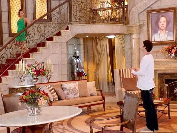 A loira aparece no alto da escada e deixa Nando sem saída (Foto: Guerra dos Sexos / TV Globo)