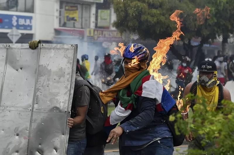 Manifestante atira coquetel molotov contra a polícia durante protesto em Cali — Foto: Luis Robayo/AFP