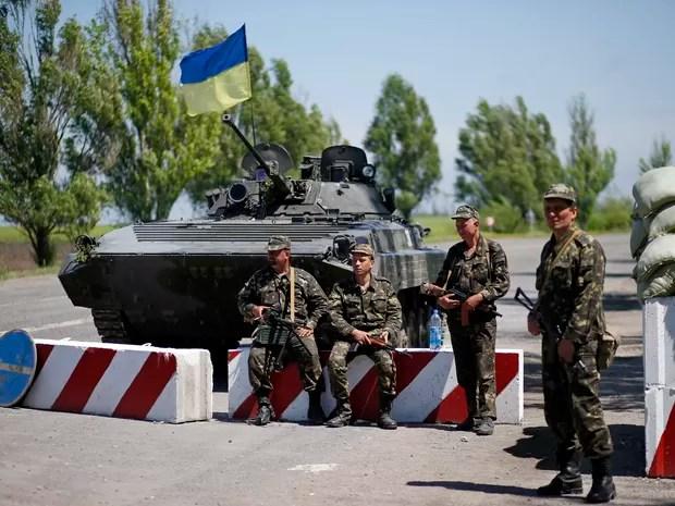 Militares ucranianos se reúnem em um posto de controle do lado de fora da cidade portuária do sudeste de Mariupol  (Foto: Reuters/Marko Djurica)