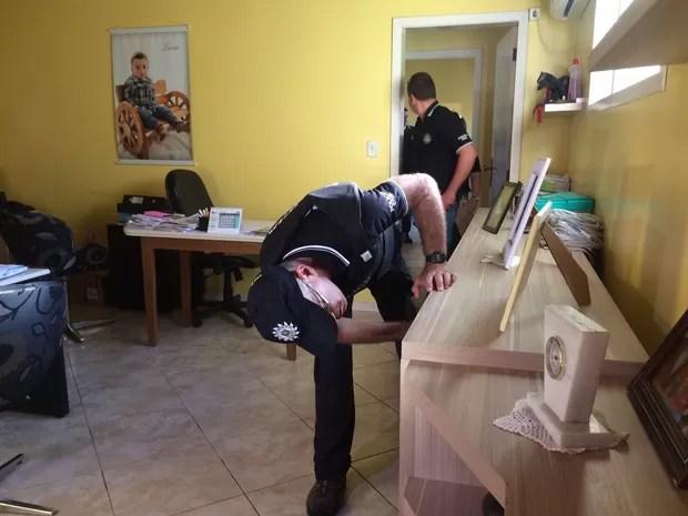 Agentes durante as buscas no escritório do motel (Foto: Fábio Almeida/RBS TV)