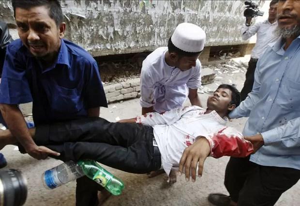 Homem ferido durante protestos de partidos islâmicos em Dhaka, capital de Bangladesh (Foto: AP Photo/Pavel Rahman)