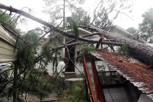 Melvin Gatlin Jr. observa nesta sexta-feira (2) estragos causados por tempestade no quintal da casa de seu pai em Valdosta, na Geórgia (Foto: Russ Bynum/AP)