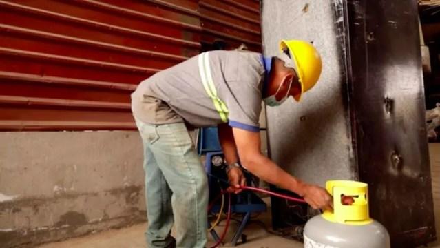Um trabalhador da empresa de Toledo extrai gases refrigerantes de um eletrodoméstico antigo — Foto: BBC