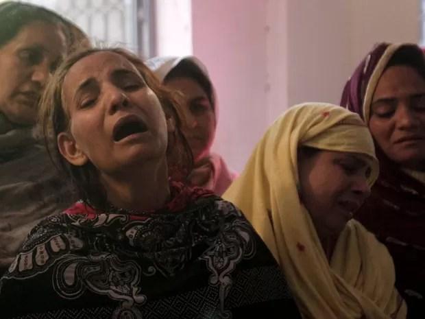 Familiares choram a morte de vítima de ataque perto de parquet em Lahore, no Paquistão, que aconteceu no domingo (27) (Foto: Mohsin Raza/ Reuters)