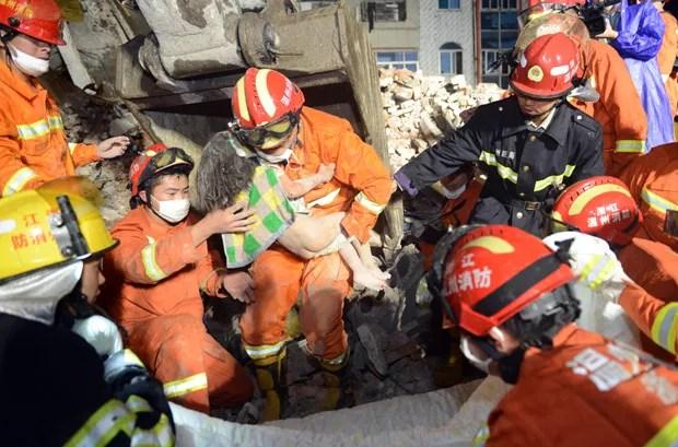 Criança, com ferimentos leves, passou mais de 12 horas sob os escombros (Foto: AFP)