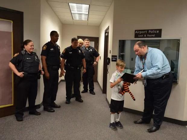 Foto mostra o garoto recebendo de volta seu tigre de pelúcia, Hobbes (Foto: Reprodução/Facebook/Tampa Internacional Airport)