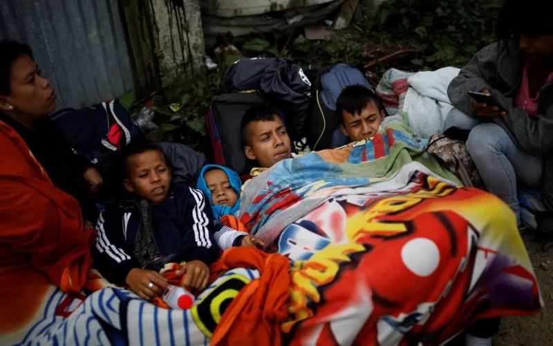 A venezuelana Maria Sanchez (esquerda) e seu filho José descansam ao lado de Johana Narvaez e dos filhos dela, Johnjairo, Jhonaderson e Jhonaiker, enquanto se protegem do frio em La Laguna, na Colômbia, em 27 de agosto — Foto: Reuters/Carlos Garcia Rawlins