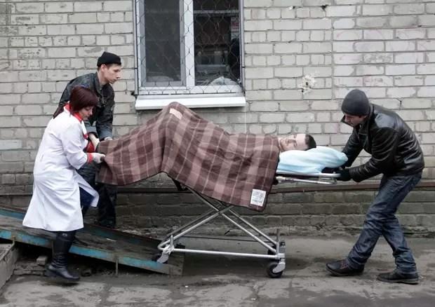 Soldado ucraniano ferido é levado de maca para hospital em Artemivsk, na Ucrânia (Foto: Petr David Josek/AP)