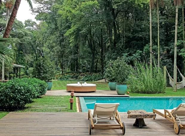 Um caminho com maciço de gardênias, dormentes e balizadores de cerâmica une os dois deques de madeira criados entre a piscina. Nos vasos, camélias. Ao lado, orquídeas-bambu (Foto: Raphael Briest/Divulgação)