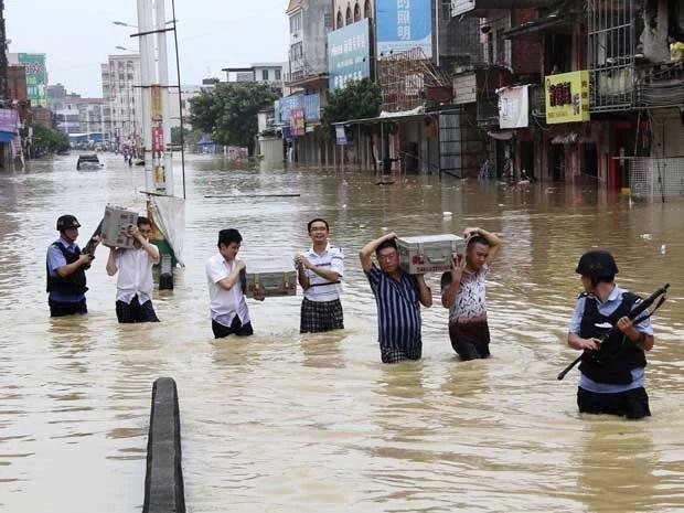 Grupo é forçado a levar dinheiro em caixas por região alagada na China, após pasagem do Tufão 'Utor'. (Foto: Reuters)