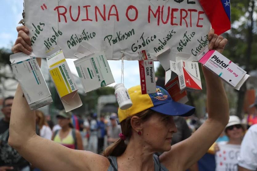 Opositora de Nicolás Maduro de Caracas segura cartaz com a mensagem 'ruína ou morte' em crítica contra a falta de medicamentos na Venezuela — Foto: Martin Mejia/ AP