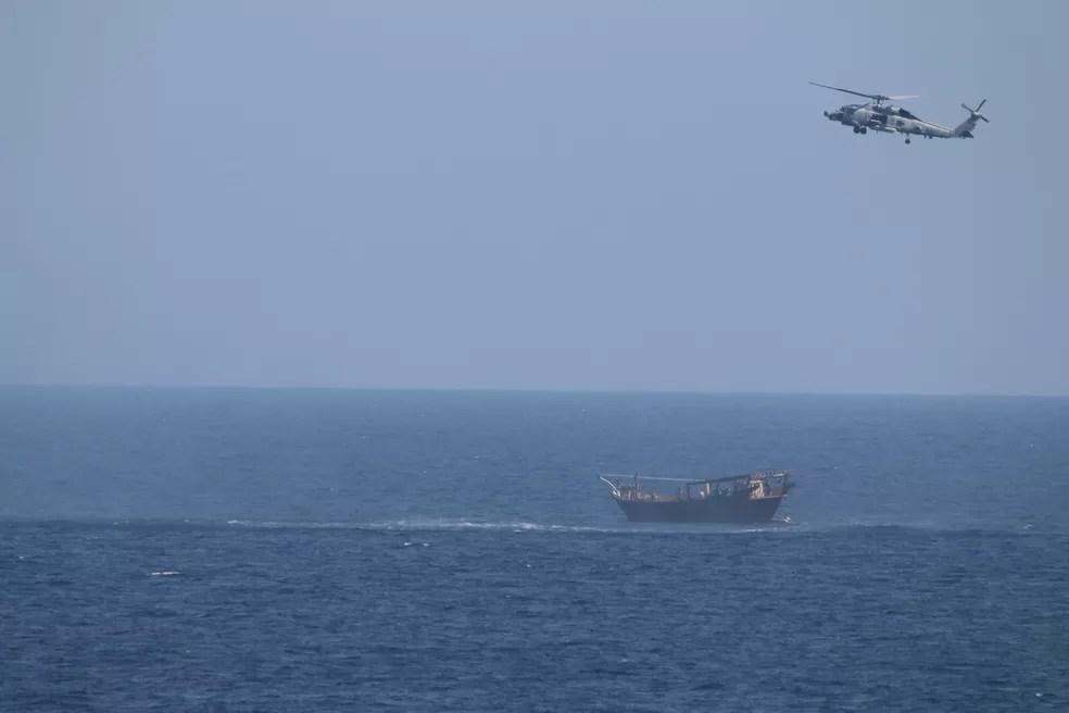 Helicóptero SH-60 Seahawk voa acima da embarcação que levava carregamento de armas apreendidas no Mar da Arábia — Foto: Marinha dos EUA via Reuters