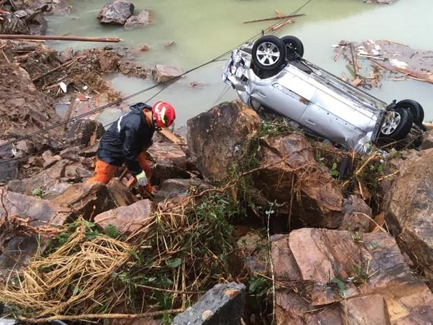 Resgatista trabalha próximo a carro virado por deslizamento de terra provocado pelas fortes chuvas trazidas pelo tufão Megi, em Sucun, na província chinesa de Zhejiang. (Foto: Reuters/Stringer)