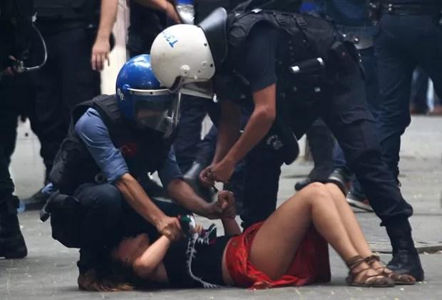 Manifestante é detida por policiais turcos durante manifestação  (Foto: Adem Altan/AFP)