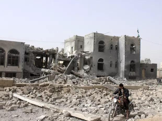 Homem monta em motocicleta em frente a sede dos houthis, destruída após ataque aéreo da coalizão liderada pela Arábia Saudita, em Saada, norte do Iêmen, domingo (26) (Foto: Stringer/Reuters)
