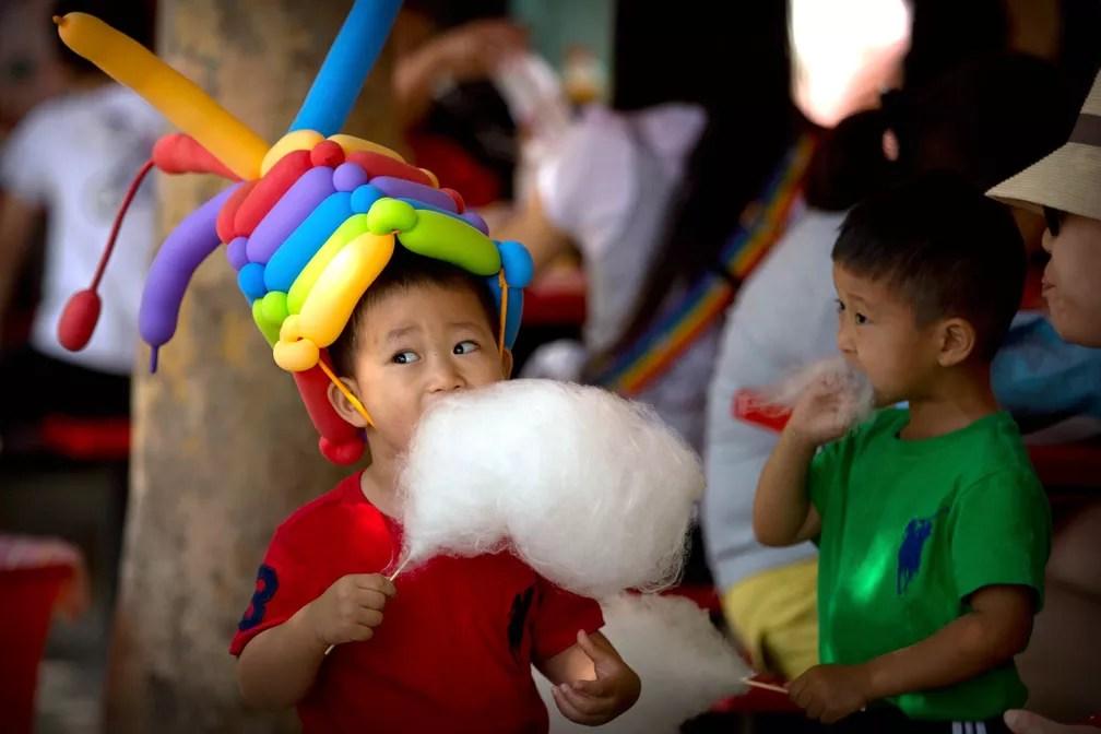 Menino com um chapéu de balões come algodão-doce em um parque de Pequim, na China, em evento que marca o Dia Internacional das Crianças, celebrado em diversos países (Foto: Mark Schiefelbein/AP)