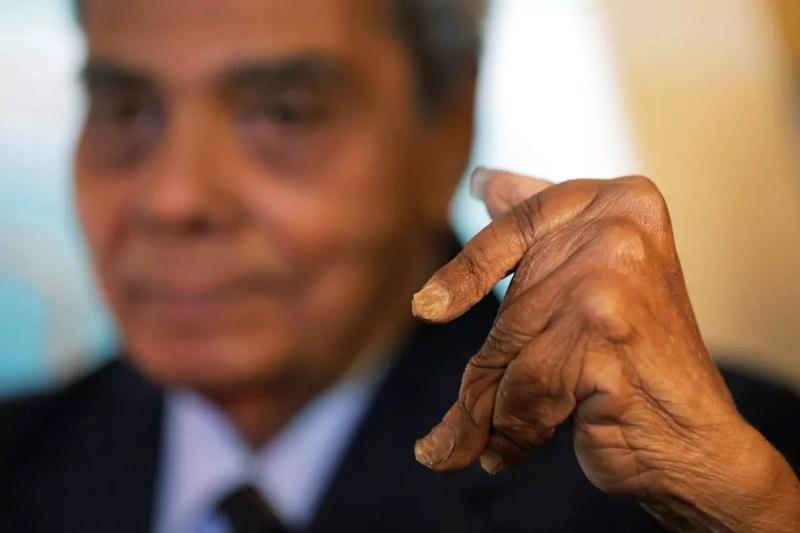 Shridhar Chillal mostra a mão com as unhas recém-cortadas após 66 anos cultivando-as. Ele perdeu a capacidade de mover os dedos após as décadas cultivando as unhas (Foto: Lucas Jackson/Reuters)