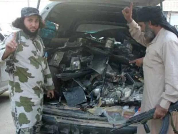 Militantes do Estado Islâmico com os restos do que dizem ser um drone americano que caiu em Raqqa  (Foto: AFP)
