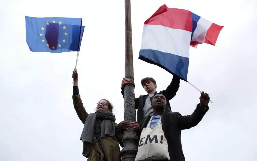 Apoiadores de Macron celebram em Paris com bandeiras da França e da União Europeia (Foto: Buhran Ozbilici/AP Photo)