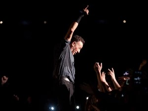 Bruce Springsteen ergue o braço em gesto característico e exibe marca de batom na bochecha durante show em São Paulo (Foto: Caio Kenji/G1)
