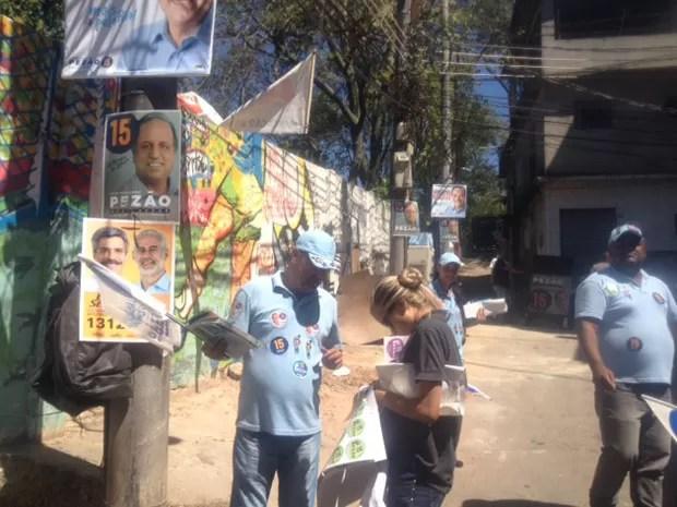 Cartazes de candidatos estavam espalhados em postes públicos da comunidade (Foto: Janaína Carvalho / G1)