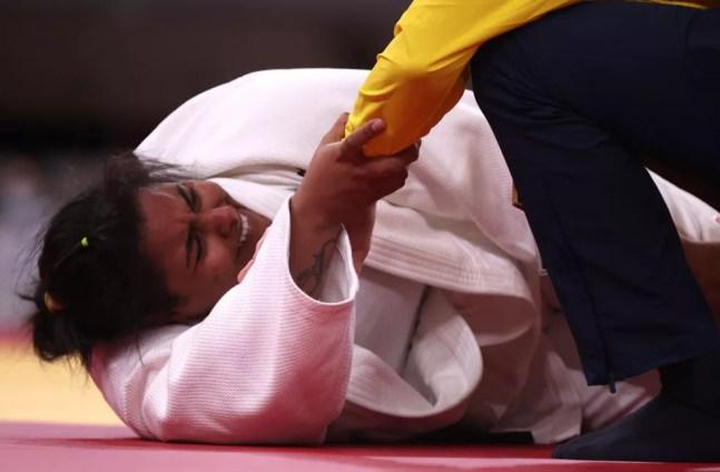 Maria Suelen Altheman segura no braço do médico da seleção brasileira após sentir lesão nas Olimpíadas de Tóquio — Foto: Chris Graythen/Getty Images