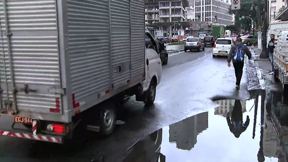 Pedestres passam pela rua, em função de alagamento (Foto: Reprodução/TV Globo)