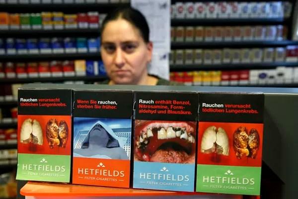 Dona de tabacaria em Berlim, na Alemanha, expõe maços de cigarro com capas de alertas para os danos à saúde causados pelo fumo, como problemas nos pulmões e nos dentes. A União Europeia planeja que em 2015 todos os maços de cigarro vendidos em seus países possuam ilustrações sobre os riscos à saúde (Foto: Fabrizio Bensch/Reuters)