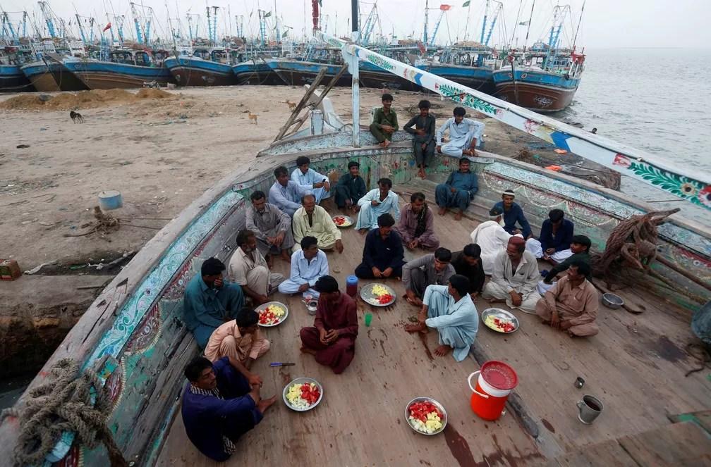 1º de junho - Pescadores são vistos em um barco de pesca enquanto se preparam para quebrar seu jejum do mês do Ramadã, em Ibrahim Hyderi, nos arredores de Karachi, Paquistão (Foto: Akhtar Soomro/Reuters)