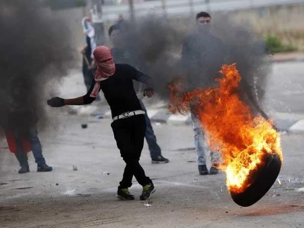 Palestino mascarado começa a queima de pneus durante os confrontos após um comício de comemoração d a 'Nakba', que embra a criação de Israel em 1948 e o êxodo de 760 mil pessoas (Foto: AP Photo / Majdi Mohammed)