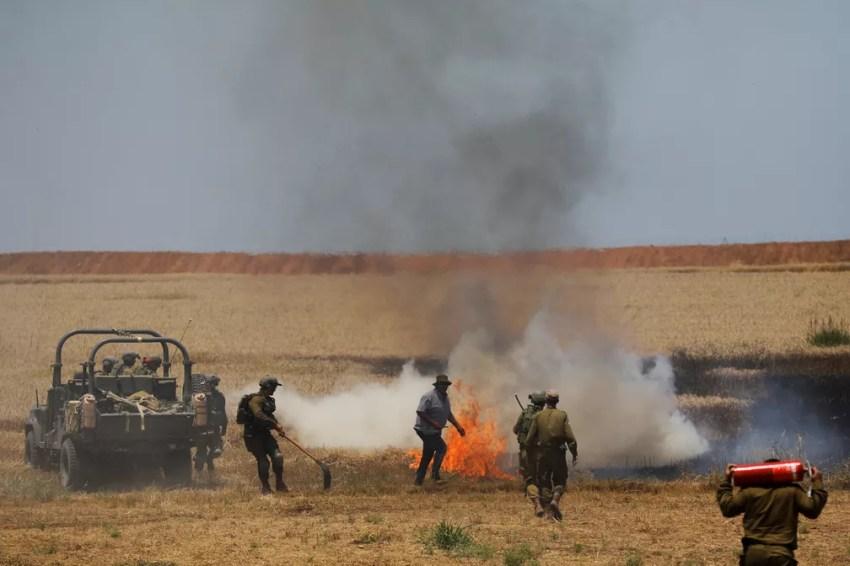 Soldados israelenses tentam apagar um incêndio em um campo do lado israelense da fronteira com Gaza (Foto: Amir Cohen/Reuters)