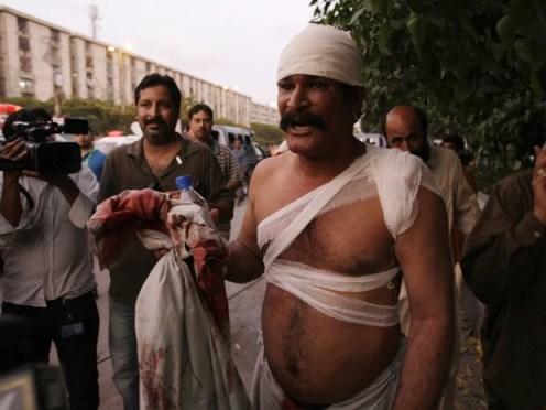Homem ferido após explosão neste sábado (20) em Karachi, no Paquistão (Foto: AP/Fareed Khan)