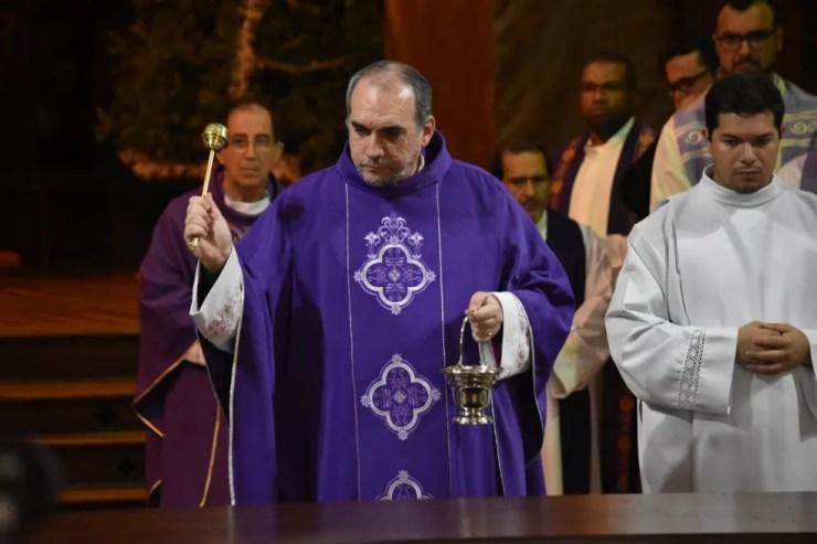 Dom Rafael Capelato, monsenhor da Catedral, asperge água benta a igreja e o público, um dia após a tragédia. — Foto: Fernando Evans/G1