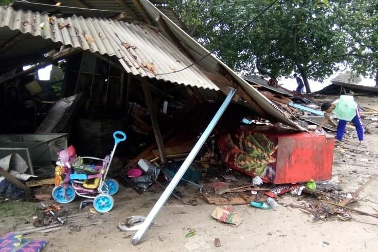 Pessoas buscam pertences em meio a destruição causada por tsunami na praia de Carita — Foto: SEMI / AFP