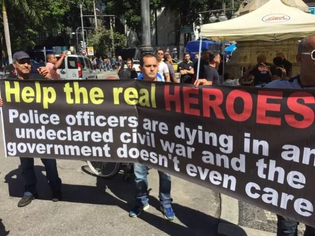 Manifestantes exibem faixa em inglês na entrada da Alerj, no Rio (Foto: Fernanda Rouvenat/ G1)