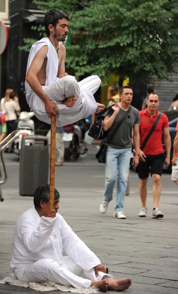 Um artista de rua parecia levitar durante um apresentação na terça-feira (26) em uma praça em Madri, na Espanha. (Foto: Dominique Faget/AFP)