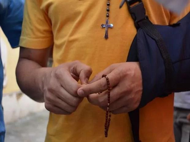 Ex-prefeito de Capela carrega um terço no pescoço e outro na mão durante transferência para presídio nesta segunda-feira (11) (Foto: Marina Fontenele/G1)