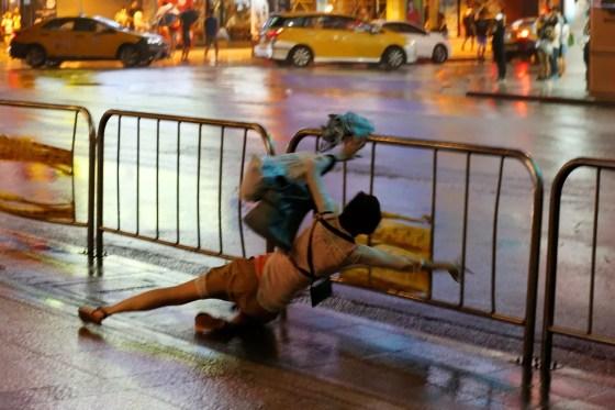 Mulher cai e se segura a uma grade durante a passagem do tufão Nesat em Taiwan, neste domingo (30) (Foto: Reuters/Tyrone Siu)