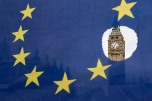 Manifestante faz protesto com bandeira da União Europeia em frente ao Parlamento britânico enquanto Theresa May anunciava, na manhã desta quarta-feira (29), o afastamento do bloco  (Foto: Oli Scarff / AFP)