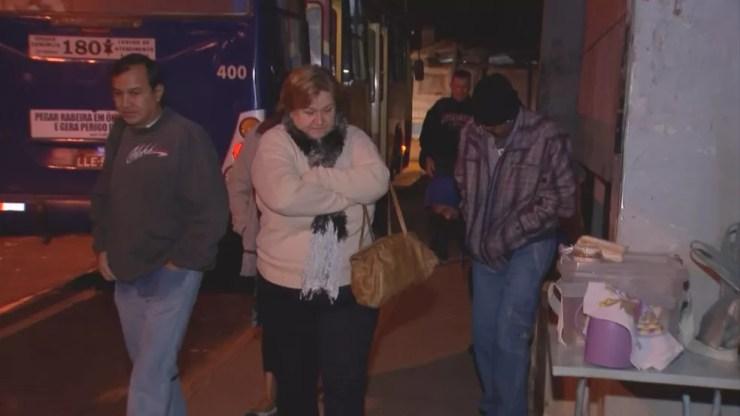 Moradores se agasalham para espantar o frio na espera do ônibus (Foto: Reprodução/TV TEM)