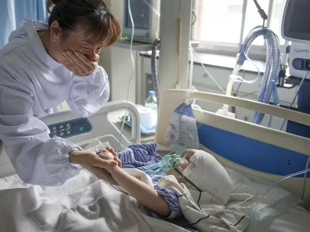 Mulher se emociona segurando a mão da menina Hanhah, de 3 anos, após ela se recuperar de uma cirurgia na qual 3 peças de titânio substituíram parte de seu crânio em Changsha, na China. A menina sofre de hidrocefalia e precisará passar por novas operações (Foto: Reuters/Stringer)
