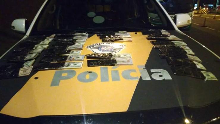 Cerca de 110 mil dólares estavam em fundo falso de mala de passageiro (Foto: Polícia Rodoviária/Divulgação )