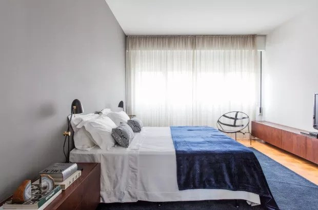 Suíte do casal. Diante da parede pintada de cinza, a cama, com roupa da Trousseau, é ladeada por minicômodas de imbuia e linhas retas, assinadas pelos arquitetos – assim como o móvel à frente. As luminárias de mesa são da La Lampe  (Foto: Maíra Acayaba / Editora Globo)