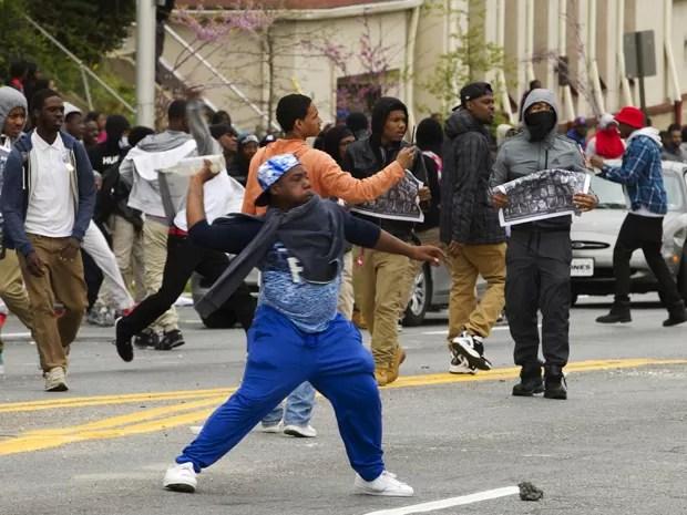 Manifestantes atiram pedras na polícia após o funeral de Freddie Gray, na Igreja Batista New Shiloh, em Baltimore, na segunda (27)  (Foto: AP Photo/Jose Luis Magana)
