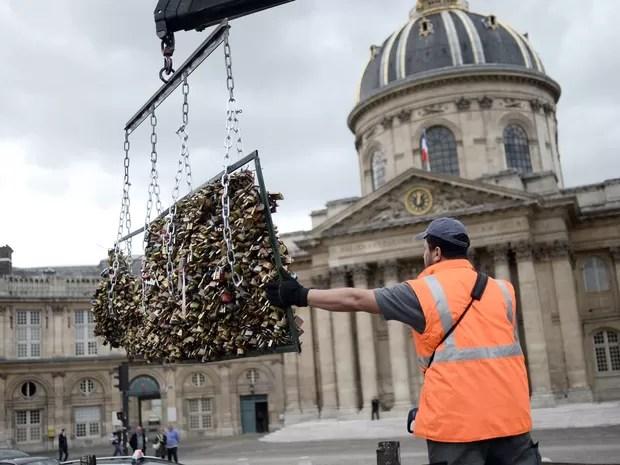 Um trabalhador remove os 'cadeados do amor' da Pont des Arts em Paris, na França. O ritual começou com turistas em 2008 e logo se espalhou para cidades como Nova York, Seul e Londres. Cerca de 1 milhão de cadeados pesando 45 toneladas serão removidos (Foto:  Stephane De Sakutin/AFP)