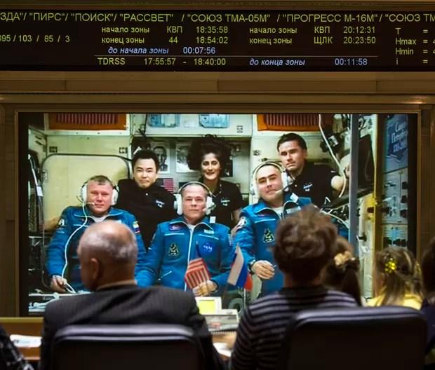 Equipe do centro de controle da missão ISS, localizado em Korolev, na Rússia, conversa com os tripulantes da Estação. Na frente, vestidos de azul, os astronautas recém-chegados; atrás, os tripulantes mais antigos (Foto: AP Photo/NASA,Bill Ingalls)